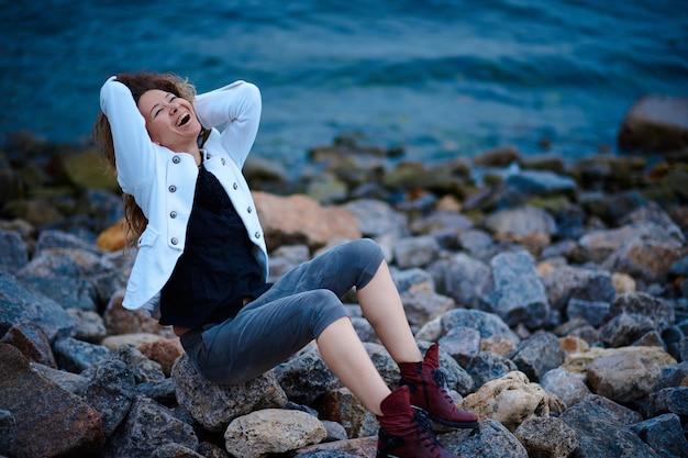 夕方に海の近くでポーズをとる白いジャケットと広いズボンに身を包んだファッショナブルな女の子