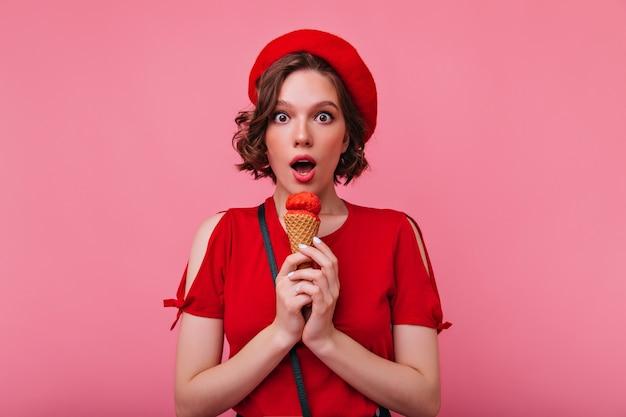 아이스크림을 먹고 놀라움을 표현하는 유행 소녀. 세련된 빨간 베레모에 사랑스러운 프랑스 아가씨의 실내 사진.