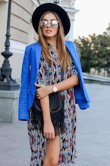 Ragazza alla moda in vestito elegante di autunno che cammina durante le vacanze in europa. elegante borsa in pelle. giacca blu e cappello nero.