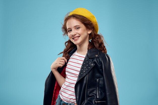 Модная девушка в черной куртке с желтым билетом полосатой футболке синем фоне