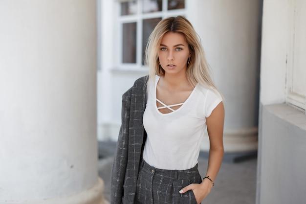 거리에 회색 빈티지 코트와 세련된 흰색 티셔츠에 유행 소녀