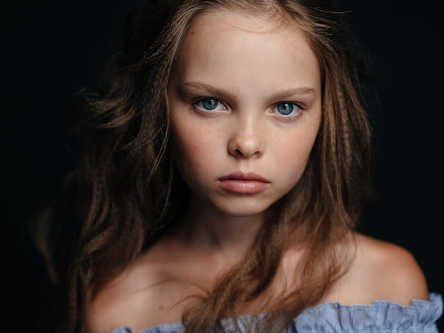 Модная девушка в сарафане на темном фоне вьющимися волосами голубыми глазами