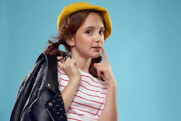 黄色のベレー帽と革のジャケットの縞模様のtシャツのファッショナブルな女の子