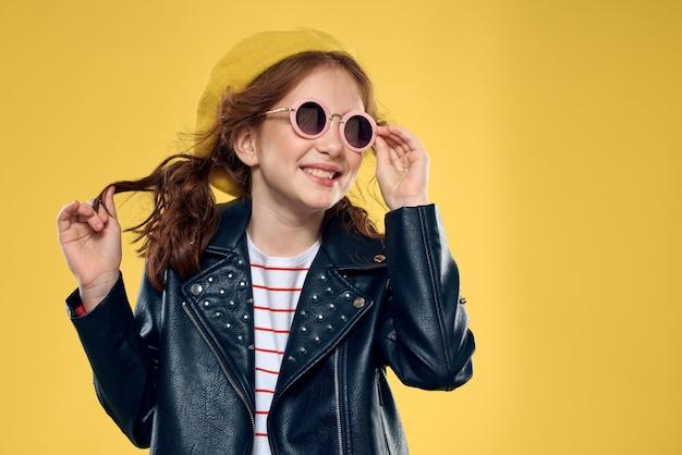 黄色い帽子メガネ服スタジオ黄色の背景でファッショナブルな女の子。高品質の写真