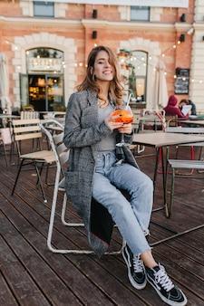 居心地の良い屋外カフェで飲み物のガラスと一緒に座っている黒い半靴のファッショナブルな女の子