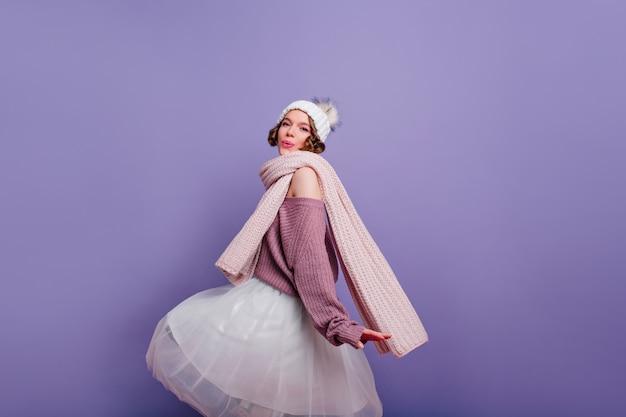 Модная девушка в длинном шарфе развлекается на фотосессии в помещении. очаровательная дама в пышной юбке и вязаной шапке танцует на фиолетовой стене.