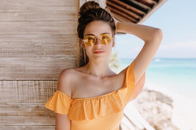 해변에서 여가 시간을 보내는 세련된 선글라스 유행 소녀. 열정적 인 백인 여성 모델의 야외 사진은 방갈로 근처에 서서 관심을 가지고 포즈를 취하는 주황색 수영복을 착용합니다.