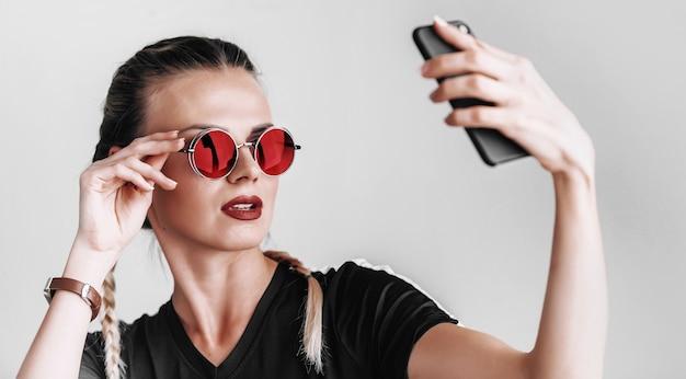 색안경을 쓴 선글라스를 끼고 휴대폰으로 셀카를 찍는 세련된 소녀