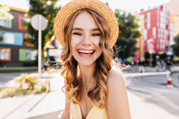 Модная девушка смеется во время отдыха в летний день. блаженная кавказская женская модель, наслаждающаяся отпуском.