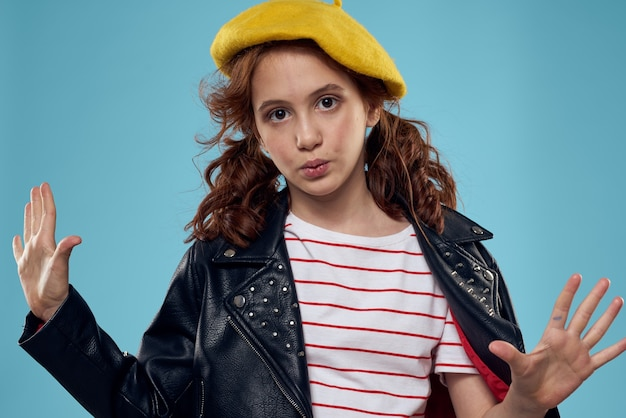 A fashionable girl in a leather jacket and a yellow hat on a blue background gestures