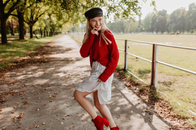心からの陽気な笑顔で魅力的に見えるファッショナブルな女の子。森の小道で楽しさを見せてくれる季節の服を着た美しい金髪。
