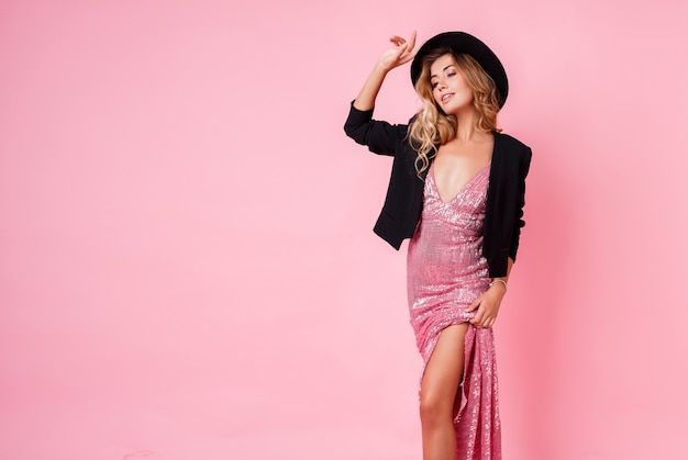 Fashionable girl in pink party dress with sequin posing on pink wall. elegant outfit. hight fashion look.