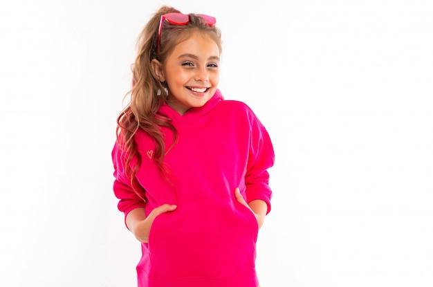 Fashionable girl in pink sweatshirt, pink sunglasses is happy and holds her hands in pockets, isolated on white background