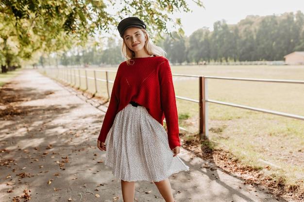 紅葉の近くでポーズをとるファッショナブルな女の子。