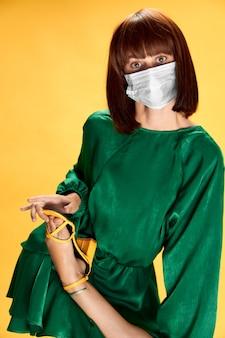手袋と保護医療マスクでポーズをとるファッショナブルな女の子