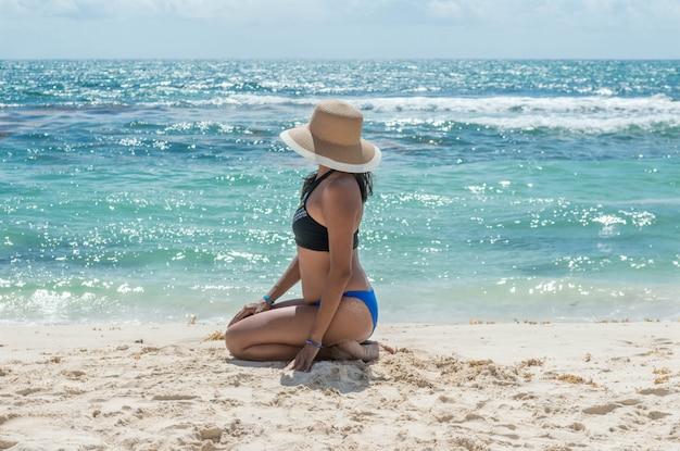 正面の後ろに海と美しい午後に青い海を見て座っているファッショナブルな女の子。太陽の帽子を持つ女性。リビエラマヤの日焼けした女性。休暇の概念。