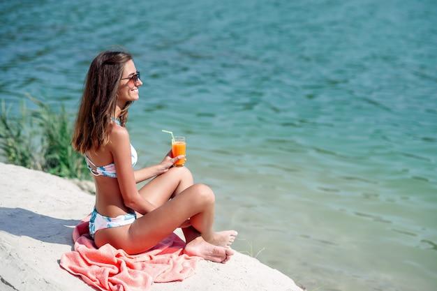 유행 소녀는 격자 무늬에 앉아서 해변에서 칵테일을 마시는. 세련 된 선글라스와 해변에서 파라다이스 휴가를 즐기는 패션 비키니에 행복 한 빠져 있 었 단된 여자.