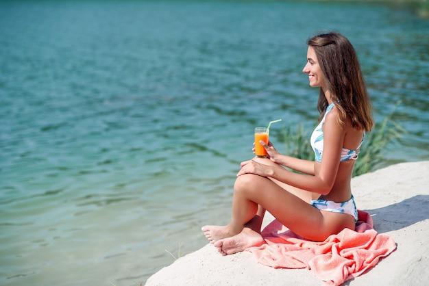 格子縞の上に座って、ビーチでカクテルを飲んでファッショナブルな女の子。スタイリッシュなサングラスとビーチで楽園の休暇を楽しんでいるファッションビキニで幸せな日焼けした女性。