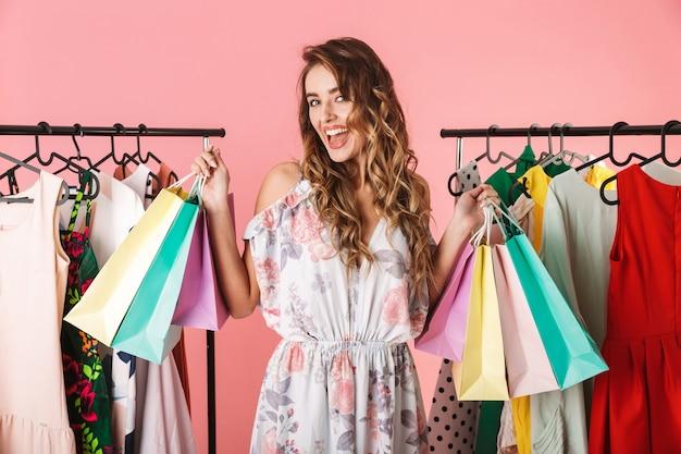 Модная девушка стоит в магазине возле вешалки и держит разноцветные сумки для покупок, изолированные на розовом