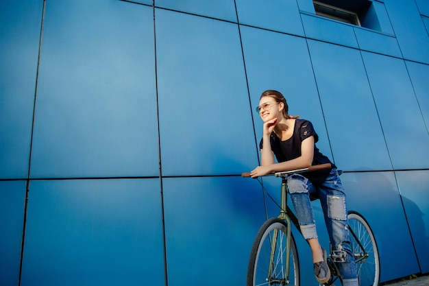 Fashionable girl in sunglasses having fun while walking with bike outdoors, wearing jeans and t-shirt.