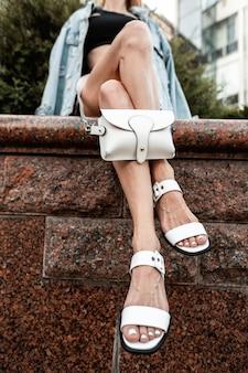 가죽 가방이 달린 세련된 흰색 빈티지 샌들에 청바지 재킷을 입은 아름다운 다리를 가진 세련된 소녀가 거리에서 쉬고 있습니다.