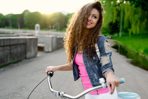 Fashionable girl with a beautiful smile rests and rides a bicycle in the summer in the city along the embankment