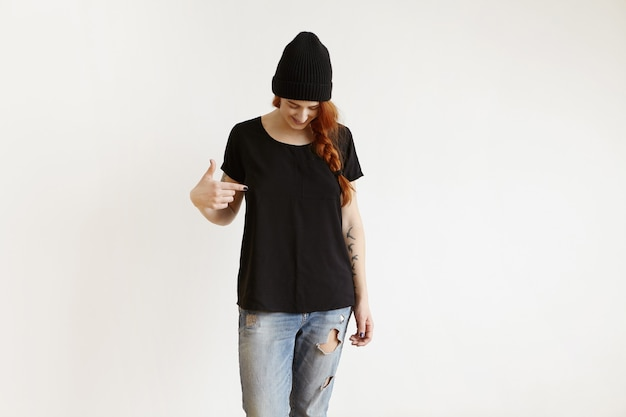 Fashionable girl with braid posing indoors in black hat and ragged jeans, pointing her finger at t-shirt