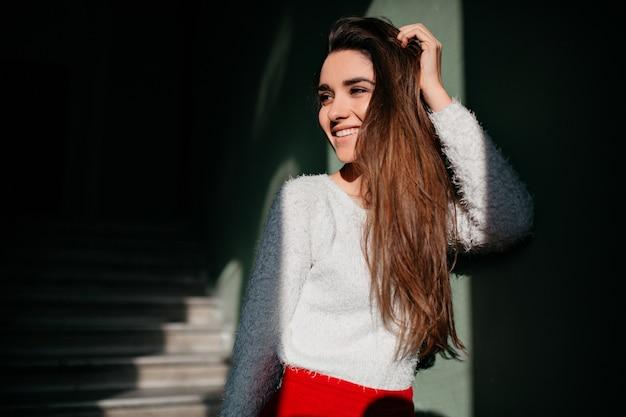 Модная девушка с длинными каштановыми волосами смотрит в сторону с милой улыбкой