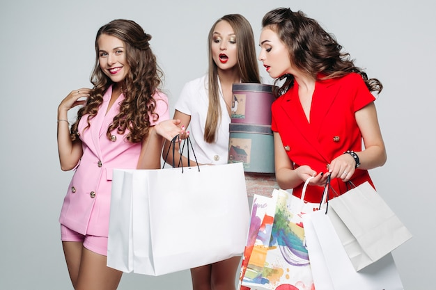 Fashionable girlfriends after shopping surprised looking inside bags.