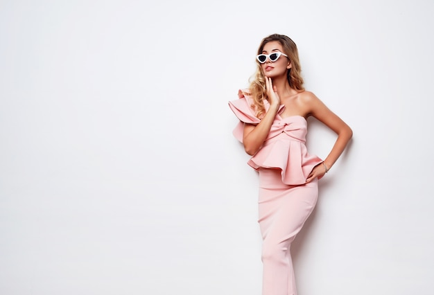 Fashionable glamorous woman in stylish sunglasses and pastel pink cocktail dress. perfect tan body.