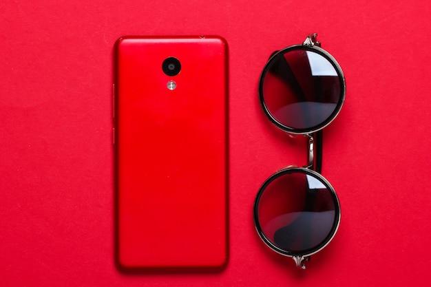 赤のファッショナブルなメガネとスマートフォン。レディースアクセサリー