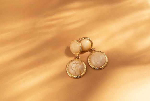 ファッショナブルなゴールドの手作りイヤリング。フラットレイ、トップビュー、日光の影のあるミニマリストファッションジュエリー。