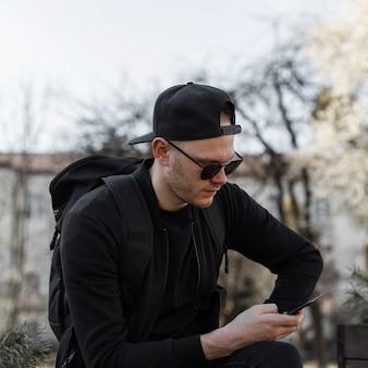 Модный красивый молодой человек в стильных солнцезащитных очках в кепке в черной одежде с портфелем сидит и смотрит на мобильный телефон в городе в солнечный день. привлекательный турист парень отдыхает на улице.