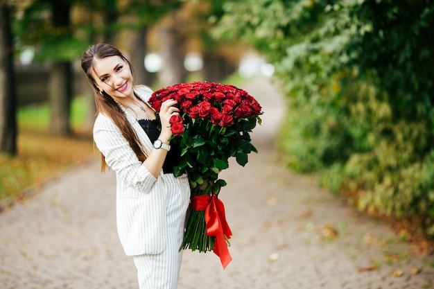 Модная шикарная сексуальная девушка в элегантном костюме держит букет из сотен красных роз. счастливого дня святого валентина.