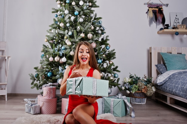 Fashionable gorgeous woman at red long evening dress posed  against new year tree with gifts. christmas holidays theme.