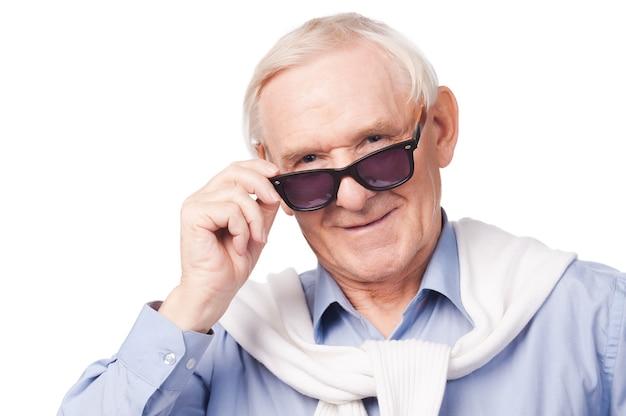 ファッショナブルな祖父。サングラスをかけ、白い背景に立ってカメラを見ているスタイリッシュな年配の男性