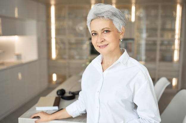 Fashionable gray haired female real estate agent in white shirt posing indoors. happy stylish woman manager standing at office desk during working day