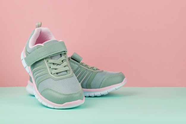 Fashionable gray sneakers on a blue and pink