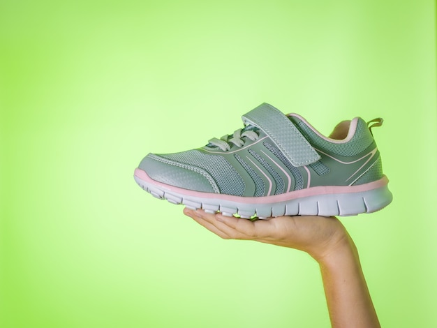 Fashionable gray sneakers in a child's hand on a green background. sports shoes. color trend.
