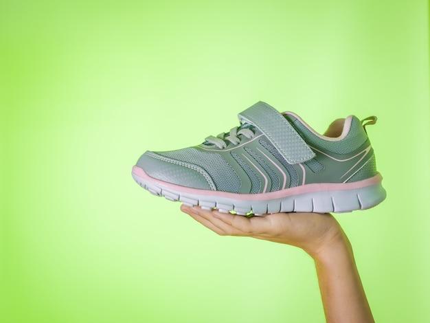 녹색 배경에 어린이 손에 유행 회색 운동 화. 스포츠 신발. 컬러 트렌드.