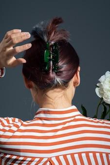 Модная зеленая шпилька в волосах девушки на сером фоне.