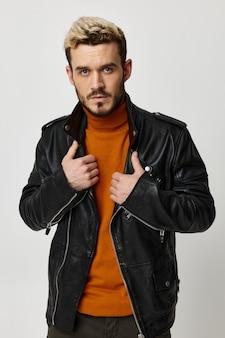 革のジャケットとオレンジ色のセーターを着たファッショナブルな男がライトに手を当ててジェスチャー