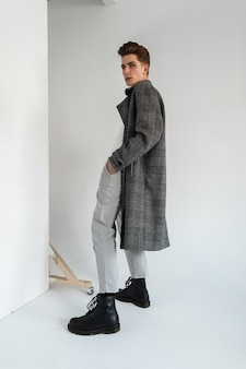 Fashionable guy in a stylish classic coat with trousers and boots in the studio