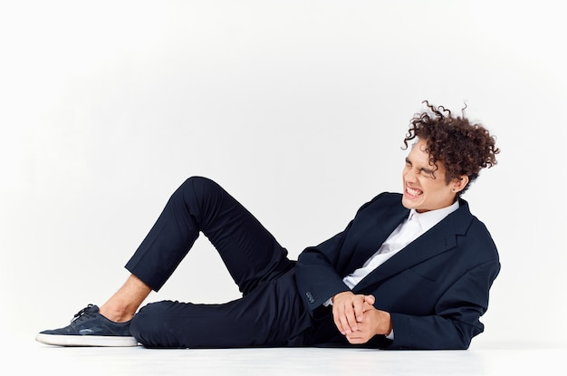 A fashionable guy in trousers and a jacket lies on the floor in a bright room curly hair sneakers