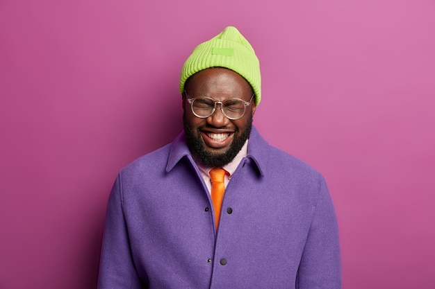 검은 건강한 피부를 가진 세련된 남자, 코믹 재미있는 상황을 듣고 웃으며 웃고 하얀 치아를 보여주고 얼굴을 가늘게 뜨고 눈을 감고 모자와 재킷을 입습니다.