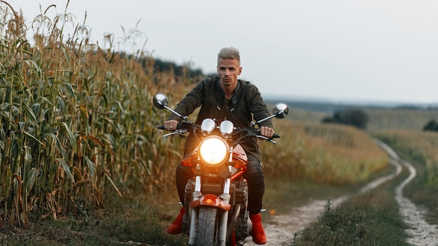 Fashionable handsome brutal man in a khaki jacket rides a motorcycle in a cornfield