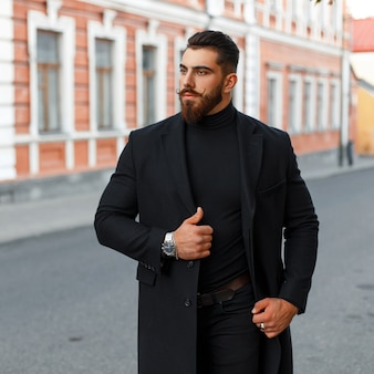 Fashionable handsome hipster man with a beard and mustache in a black coat on the street