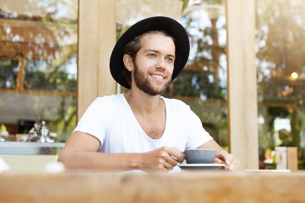 Модный красивый студент-мужчина с густой бородой сидит за деревянным столом с кружкой и пьет кофе, имея счастливое и веселое выражение лица