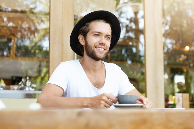 Fashionable handsome male student with thick beard sitting at wooden table with mug and drinking coffee, having happy and cheerful face expression