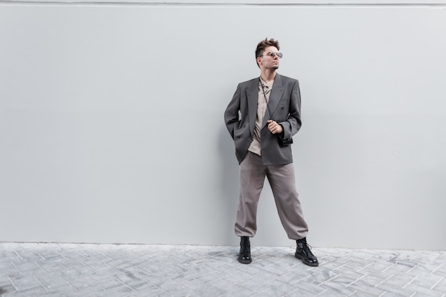 Fashionable handsome man model in stylish casual look with a shirt, jacket, trousers and boots stands near a gray wall in the city. free space for text and logo